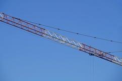 抽象图象,一部分的胳膊机械建筑用起重机有蓝天背景 免版税库存照片