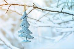 抽象圣诞树,垂悬在一个积雪的分支在公园 免版税库存图片