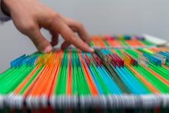 抽象在抽屉的背景五颜六色的垂悬的文件夹 供以人员手查寻文件 免版税库存图片