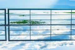 抽象大阳台云彩的湖边、在步行者的反射和天空蔚蓝在雨以后,发光在湖的日落光 库存图片