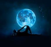 抽象妇女是瑜伽在与星的蓝色满月在黑暗的夜 库存图片