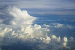 抽象密集的软的蓬松白色云彩copyspace看法与蓝天和地球背景树荫的从飞行飞机上的 免版税库存照片