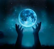 抽象手,当祈祷在与星的蓝色满月在黑暗的夜空背景中时 免版税图库摄影