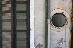 抽象有木绿色快门、圆的窗口和管子的,大厦门面葡萄酒内部难看的东西背景老墙壁  库存照片