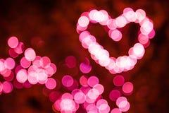 抽象梦想的精美软的defocused圈子圆的桃红色轻的照明Bokeh形式到心脏形状里 有益于背景 库存照片