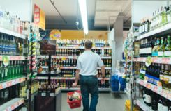 抽象模糊的超级市场 有一个红色篮子的一个人在商店做购买 购物在超级市场 免版税库存照片