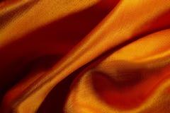 抽象橙色背景豪华布料丝绸纹理缎材料或豪华关闭 免版税库存图片