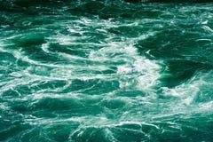抽象浪端的白色泡沫潮流在绿河中 库存照片