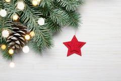 抽象空白背景圣诞节黑暗的装饰设计模式红色的星形 在白色木背景的杉树与光和红色星 免版税库存图片