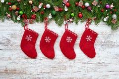 抽象空白背景圣诞节黑暗的装饰设计模式红色的星形 在白色木背景的红色圣诞节袜子与圣诞节杉树 库存照片