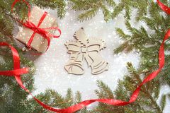 抽象空白背景圣诞节黑暗的装饰设计模式红色的星形 在白色木背景,有红色缎丝带的,木响铃, Christma礼物盒的绿色树枝框架 免版税库存图片