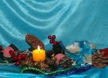 抽象空白背景圣诞节黑暗的装饰设计模式红色的星形 杉木分支,玩具,在一蓝色backg的蜡烛 图库摄影