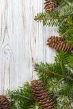 抽象空白背景圣诞节黑暗的装饰设计模式红色的星形 杉树分支杉木锥体在木桌上 平的位置,文本的空间 免版税库存图片