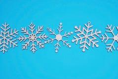 抽象空白背景圣诞节黑暗的装饰设计模式红色的星形 木激光切开了在Midle的雪花,在蓝色背景,与雪花的设计的 库存图片