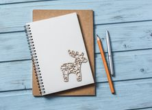 抽象空白背景圣诞节黑暗的装饰设计模式红色的星形 倒空空白的笔记薄,圣诞节装饰在蓝色木背景的驯鹿玩具 计划的圣诞节  库存图片