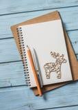 抽象空白背景圣诞节黑暗的装饰设计模式红色的星形 倒空空白的笔记薄,圣诞节装饰在蓝色木背景的驯鹿玩具 计划的圣诞节  免版税库存照片