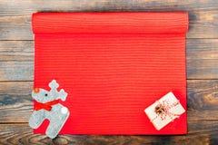 抽象空白背景圣诞节黑暗的装饰设计模式红色的星形 礼物盒平位置装饰了工艺纸、杉木锥体和鹿在一张红色纺织品桌布 免版税库存图片