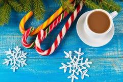 抽象空白背景圣诞节黑暗的装饰设计模式红色的星形 一杯咖啡与牛奶热奶咖啡、明亮的棒棒糖和绿色云杉的分支的在蓝色背景 免版税库存照片
