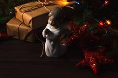 抽象空白背景圣诞节黑暗的装饰设计模式红色的星形 圣诞树分支与在wo的天使 库存图片