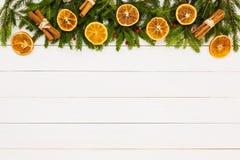 抽象空白背景圣诞节黑暗的装饰设计模式红色的星形 圣诞节杉树,在白色木背景,拷贝空间的干桔子 库存照片