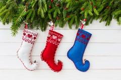抽象空白背景圣诞节黑暗的装饰设计模式红色的星形 圣诞节与装饰,在白色木背景的五颜六色的圣诞节袜子的杉树 免版税库存图片