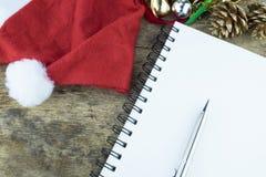 抽象空白背景圣诞节黑暗的装饰设计模式红色的星形 红色耳机在圣诞老人帽子、巧妙的电话和圣诞节装饰职员在木背景 免版税图库摄影