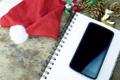 抽象空白背景圣诞节黑暗的装饰设计模式红色的星形 红色耳机在圣诞老人帽子、巧妙的电话和圣诞节装饰职员在木背景 免版税库存图片