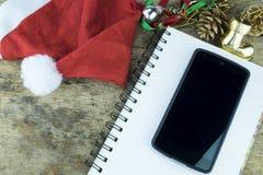 抽象空白背景圣诞节黑暗的装饰设计模式红色的星形 红色耳机在圣诞老人帽子、巧妙的电话和圣诞节装饰职员在木背景 免版税库存照片