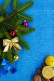 抽象空白背景圣诞节黑暗的装饰设计模式红色的星形 用五颜六色的装饰装饰的分支云杉,坚果,桂香,在蓝色餐巾的柠檬 免版税图库摄影