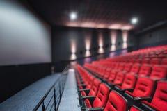 抽象红色剧院或电影位子迷离空的行  椅子在戏院大厅里 方便的扶手椅子 免版税库存照片