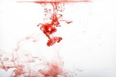 抽象红色油漆下落在水中 库存图片