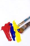 抽象红色,蓝色和黄色丙烯酸漆和刷子 免版税库存图片