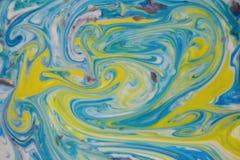 抽象背景与墨水黄色和蓝色漩涡混合了 免版税库存图片