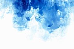 抽象背景颜色墨水下落在水中 油漆蓝色云彩在白色的 免版税库存图片