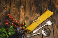 抽象背景食物意大利面食纹理 干燥意粉用乳酪、菜和草本在一张木桌上 顶视图 库存图片