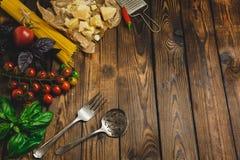 抽象背景食物意大利面食纹理 干燥意粉用乳酪、菜和草本在一张木桌上 顶视图 免版税库存图片