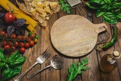 抽象背景食物意大利面食纹理 干燥意粉用乳酪、菜和草本在一张木桌上 顶视图 免版税库存照片