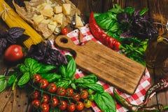 抽象背景食物意大利面食纹理 干燥意粉用乳酪、菜和草本在一张木桌上 免版税库存照片