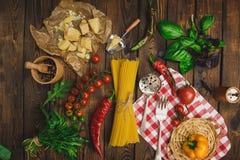 抽象背景食物意大利面食纹理 干燥意粉用乳酪、菜和草本在一张木桌上 库存图片