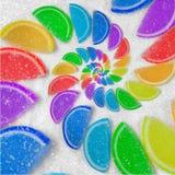抽象螺旋果冻彩虹楔住在白糖沙子背景的切片 彩虹果冻糖果 甜果冻liths 免版税库存照片