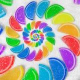 抽象螺旋果冻彩虹楔住在白糖沙子背景的切片 彩虹jelliy糖果 甜果冻liths 免版税库存图片