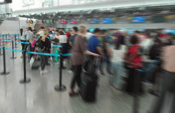 抽象迷离背景,机场与许多乘客的登记处柜台与Bokeh的队列的 库存图片