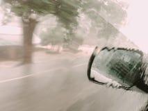 抽象迷离:下雨在车窗的边的下落,看见没有的镜子 免版税库存图片