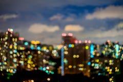 抽象都市夜,公寓,居民住房,房子 城市在与轻的bokeh,被弄脏的焦点,微明的晚上 免版税图库摄影