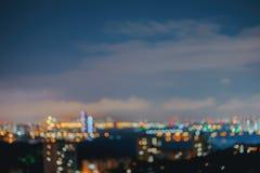 抽象都市夜 城市在与轻的bokeh的晚上反对与云彩的天空,被弄脏的焦点,暮色时刻,为 库存图片