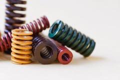 抽象金属春天五颜六色的钢螺旋盘绕用不同的坚硬灵活性大小 灰色背景,软 库存照片