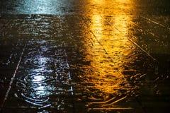抽象雨珠和飞溅声在与黄色和白色光反射的路面地板上浇灌在晚上 免版税图库摄影