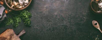 抽象食物背景 黑暗的土气厨房用桌顶视图与木切板和烹调匙子,框架的 横幅或 库存图片