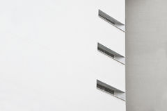 抽象结构背景 白色门面和对角窗口在一个灰色砖墙旁边 免版税库存图片