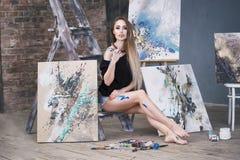 绘抽象画的年轻女性艺术家在演播室,美丽的性感的妇女画象 免版税库存照片